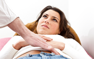 woman with physician applying pressure to her abdomen